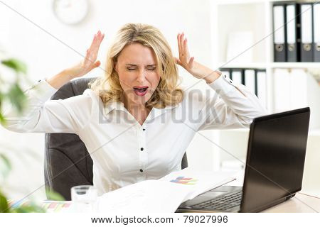 Stressed businesswoman screaming loudly at laptop in office