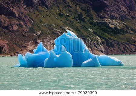 Unique lake Viedma in arid Patagonia. Huge white and blue icebergs floating in the icy water of emerald lake in Argentina.