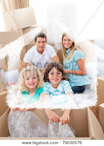 Smiling family packing boxes against house outline in clouds
