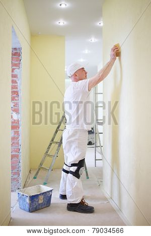 Finisher polishing the wall using a sanding sponge