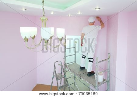 Finisher with brush in hand standing on scaffolding and painting walls in pink room