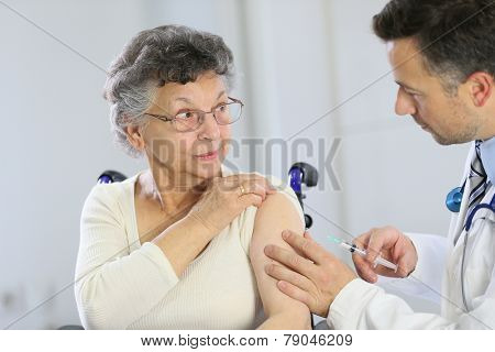 Doctor doing vaccine injection to elderly woman poster