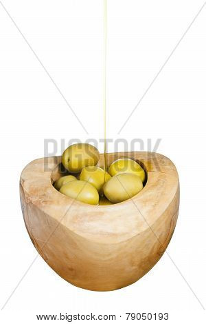Olive Oil Trickles On Green Olives In Wooden Bowl