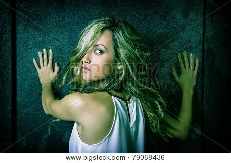 Young woman scared with her hands over a metallic door