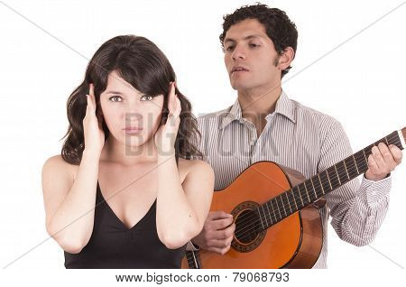 beautiful girl gesturing silence while young man serenades her with guitar