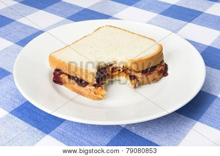A delicious peanut butter and jelly sandwich with grape jam has a bite taken out of it during lunchtime.