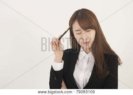 Stressed asian businesswoman with a pen