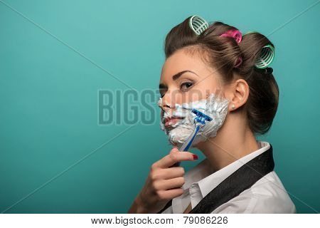 Cute brunette woman in hair curlers posing with foam on face