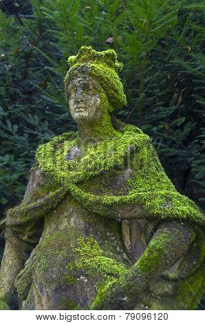 Moss-covered Stone Statue Of The Queen In The Park.