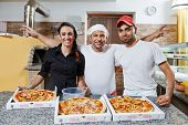 chef baker, pizza cook and waitress in uniform at pizzeria restaurant kitchen poster
