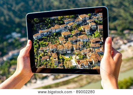 Young woman tourist photographing with tablet Berat city from the castle mountain in Albania. poster