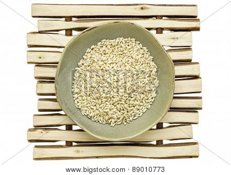 sprouted brown rice in a ceramic bowl on a wood stick trivet