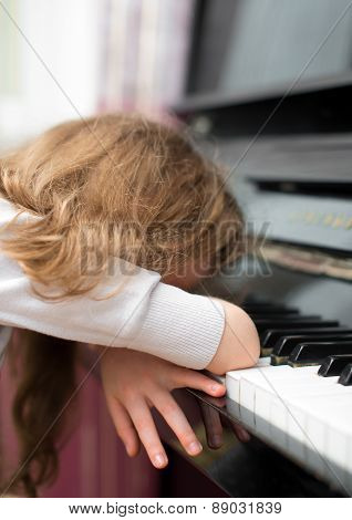 Little girl learns to play the piano.