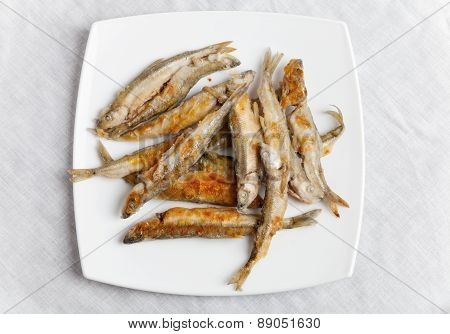Pile Of Fried Smelts Fish Lays On A White Plate, Top View
