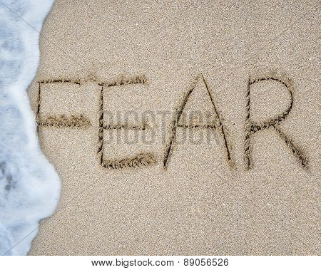 Fear word hand written with white wave foam on sand beach background poster