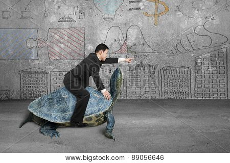 Businessman Riding Turtle And Indicating With Finger In Concrete Room