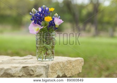 A bouquet of Texas wildflowers from the Texas Hill Country in a mason jar on a stone wall. Evening primroses bluebonnets and yellow daisies. poster