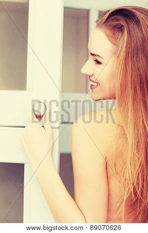 Young woman opening wardrobe doors