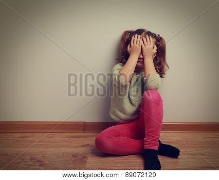 Frightened Crying Kid Girl Sitting On The Floor With Closed Face The Hands