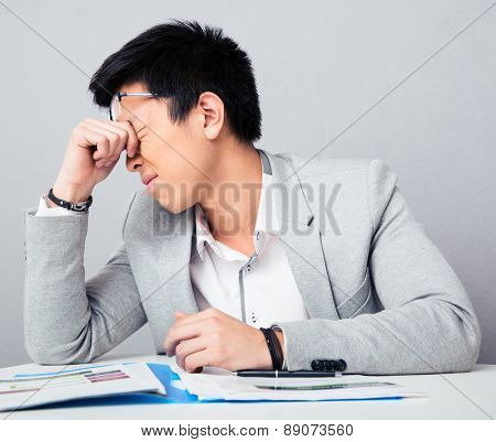 Tired businessman sitting at the table and rubbing his eyes over gray background