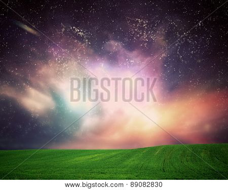 Green field of grass under dream galaxy sky, space. Glowing stars, universe light.