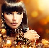 Fashion model brunette girl with golden accessories over gold shiny background. Golden Jewellery. Gold Jewelry. Beauty Egyptian Style Woman with Gold Accessories. Golden bracelet and Necklace poster