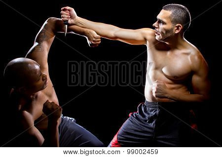 Muscular martial arts instructor demonstrating how to disarm an attacker with a knife poster