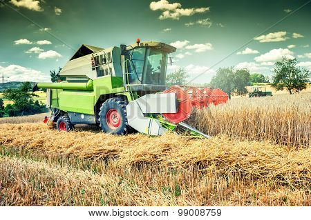 Combine Harvester Working On Wheat Field