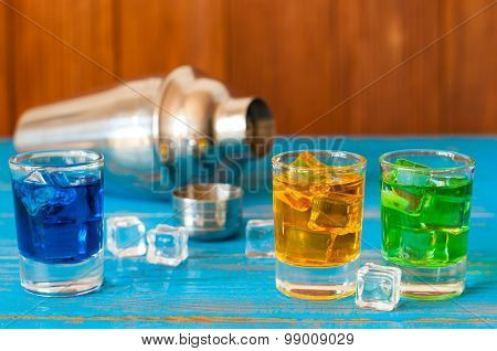 Blue, green, red alcohol or alcohol-free cocktail with ice cubes and shaker on a bar counter, wooden