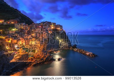 Amazing view of Manarola city at evening light with costal rocks on a foreground. Cinque Terre National Park, Liguria, Italy, Europe.