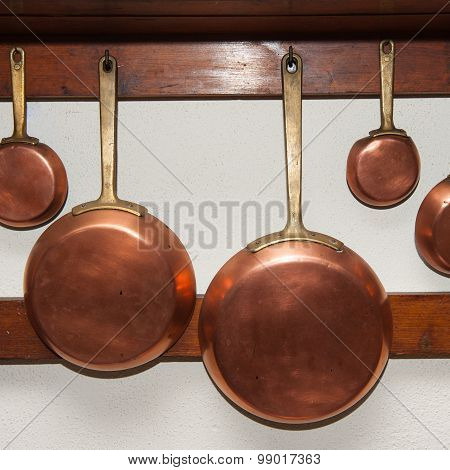 Row of vintage copper pans different size hung on wooden shelf in kitchen detail poster