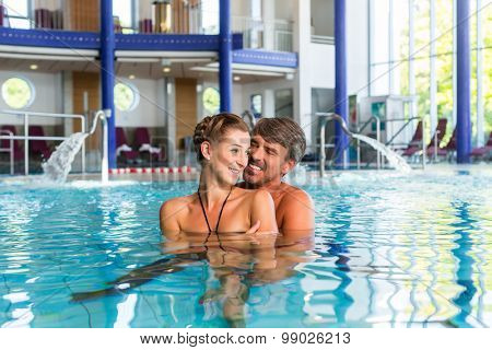 Mann and woman in pool of wellness thermal spa swimming embracing poster