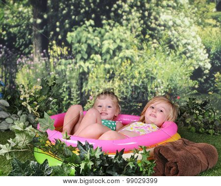 Two preschool sisters looking at the viewer as they relax outside in their filled and inflated kiddie pool.