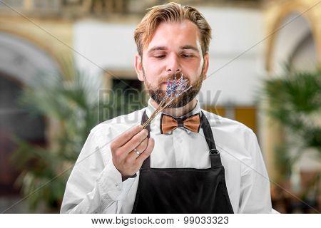 Barista smelling sprig of lavanda