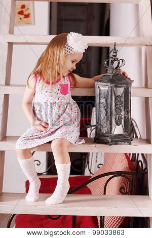 Little Cute Blond Girl In Dress Sitting On Wooden Stairs With With Old Luminaire. Focus On Lamp