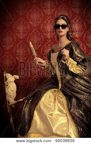 Charming girl like a Snow White in a beautiful lush dress spins on the spinning wheel.  Renaissance. Barocco. Fashion. Fairy tale.