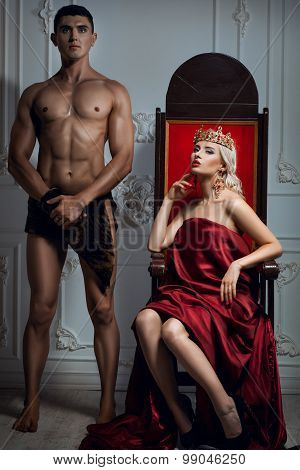 Queen Sitting On A Throne. Nearby Is An Athletic Slave.