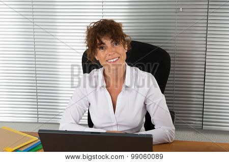 Happy Busineswoman Sitting In The Office With Laptop