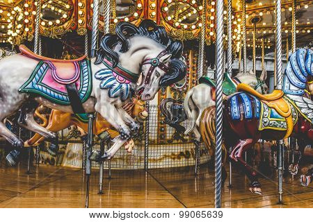 Old French Carousel In A Holiday Park. Three Horses And Airplane On A Traditional Fairground Vintage