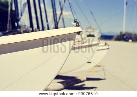 closeup of some catamaran sailboats stranded in a beach, with a filter effect
