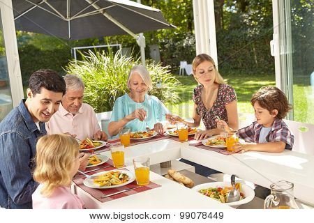 Happy family in three generations eating lunch together in summer
