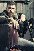 Serious unshaven male biker in leather jacket sitting near motorcycle in garage with big brown old briefcase looking forward on workshop background vertical picture poster