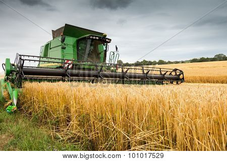 Combine Harvester At Work Harvesting Field Of Crop