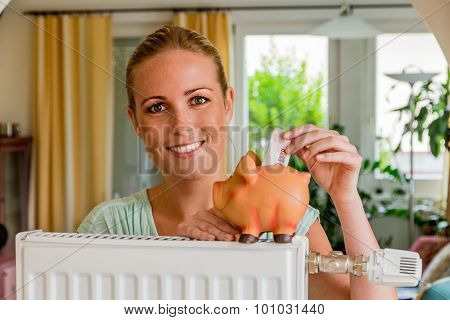 a young woman with a radiator and a piggy bank. symbolic photo for saving energy and heating