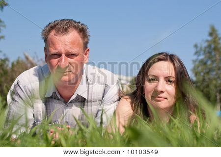 Portrait Of A Woman And A Man Lying On Grass
