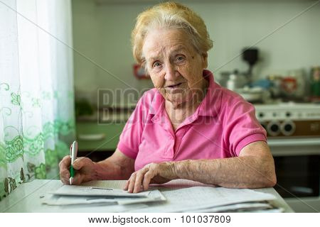 Senior woman populates handle her utility bills notices, sitting at the table in the kitchen.