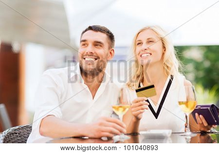 date, people, payment and relations concept  - happy couple with credit card, bill and wine glasses at restaurant terrace