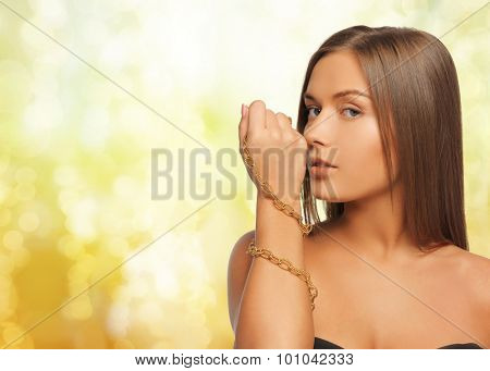 beauty, luxury, people, holidays and jewelry concept - beautiful woman with golden chainlet over hand yellow lights background