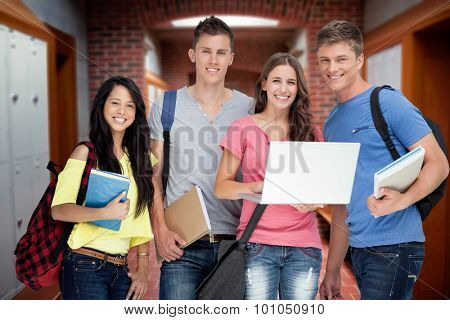 A smiling group of students holding a laptop while looking at the camera against brick walled corridor with tiled flooring in college
