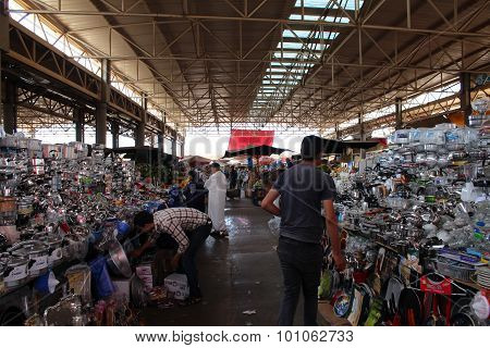 A covered market in Agadir, Morocco: utensils, fruits and vegetables.